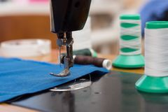 The old sewing machine is sewn blue cloth in the home workshop.  Royalty Free Stock Photo