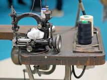 Old sewing machine on wooden base. Old black sewing machine on a wooden base Stock Photo