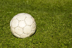 Old shabby ball on green grass Royalty Free Stock Images