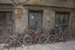 A old shabby bicycles of various sizes stand on the street near the damaged wall royalty free stock images