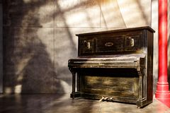 Old shabby black piano near the wall. Sunset light. Shadows on the wall royalty free stock photo