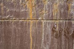 Old shabby brown rusty metal wall with a horizontal stripe, patches of white paint and dirt. rough surface texture. An old shabby brown rusty metal wall with a royalty free stock images