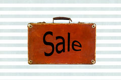 Old shabby brown suitcase watercolor blue stripes background with sign Sale on it. Stock Photo