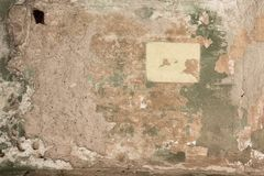 Old shabby damaged plaster on the brick walls of houses close-up stock image
