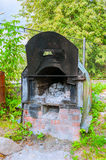 Old shabby garden stove with ash remains inside. Old iron shabby garden stove with ash remains inside Stock Photography