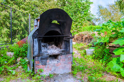 Old shabby garden stove with ash remains inside. Old iron shabby garden stove with ash remains inside Royalty Free Stock Photography