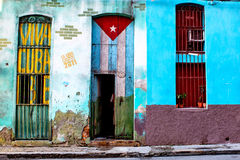 Old shabby house in Havana painted with the Cuban flag. Havana, Cuba - December 11, 2016: Old shabby house in Central Havana painted with the Cuban flag and a ` Stock Photos