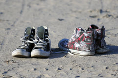Old shabby keds. Photo of old running tourist shoes on a seashore sands Stock Photography