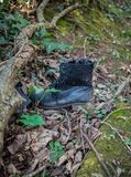 Old shabby leather black dirty boots left in wood stock photography