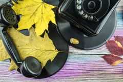 Retro phone and records lie with autumn leaves on the table. Stock Photo