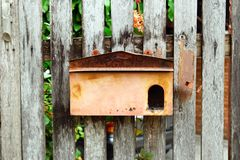 Old shabby postbox on a wooden wall. Stock Image