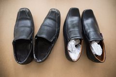 Old shabby shoes in comparison with new and expensive ones. Stock Images
