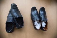 Old shabby shoes in comparison with new and expensive ones. Stock Photography