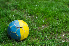 Old shabby soccer ball on grass Royalty Free Stock Images