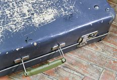Old shabby suitcase on a wooden floor Stock Photos