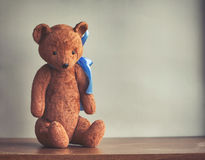 Old shabby toy bear with a blue bow Stock Images