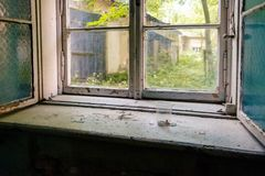Old double- glazed window opening with a crack in an abandoned b Stock Image
