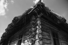 Old shabby wooden house with a broken roof near. On a background of clouds Stock Photos