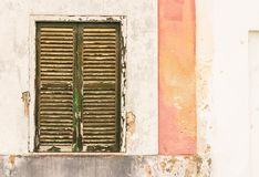Old shabby wooden window shutter with weathered wall Royalty Free Stock Images