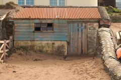 Old shack on Hope Cove beach in Devon, United Kingdom. Old shack on Hope Cove harbour beach in Devon, with rusty corrugated roof United Kingdom royalty free stock images