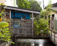 The old shacks, hovel houses stand on stilts in the water on the waterfront. Houses of poor people. Thailand Bangkok Stock Photos
