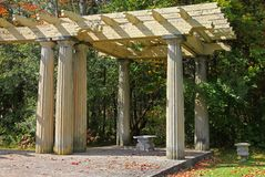 Old shaded arbor and tlegant stone bench Stock Photo