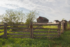 Old shed behind fence Royalty Free Stock Photo