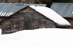 Old shed behind a snow bank. Old dark brown wood shed with two windows behind a snowbank Royalty Free Stock Photos
