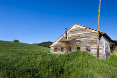 Old shed by grassy hill. Royalty Free Stock Image