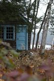Teal Shed In the Woods. An old shed with teal blue trim nestled in the woods. Shot with depth-of-field Royalty Free Stock Photo