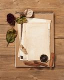 Old sheet of paper with dried rose on wooden background, spice and decoration, top view, retro style Royalty Free Stock Image