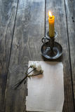 Old sheet of paper, pink rose  and candle on wooden background. Stock Images