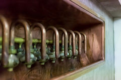 Old shiny copper taps at the brewery production Stock Photos