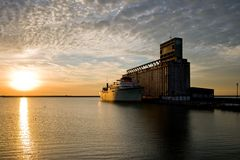 Old ship and grain elevator. An old ship and grain elevator on the waterfront at sunset royalty free stock photos