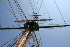 Old Ship Mast. View of an old ship mast, with sails tucked in and ropes going to all directions stock photos