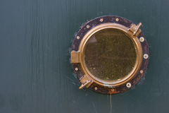 Old ship porthole. On green Royalty Free Stock Photography