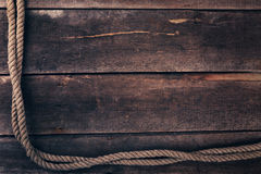 Old ship rope on wooden plank background Royalty Free Stock Images