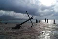 The old ship`s anchor against the gray-blue clouds. royalty free stock photo