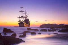 Old ship silhouette in sunset scenery stock image
