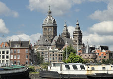Old ships in Amstel river against old Amsterdam. Old ships against old Amsterdam Stock Photos