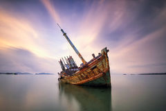 An old shipwreck or abandoned shipwreck. Wrecked boat abandoned stand on beach or Shipwrecked off the coast of Thailand Royalty Free Stock Photos