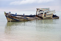 An old shipwreck or abandoned shipwreck. Wrecked boat abandoned stand on beach or Shipwrecked off the coast of Thailand Stock Images