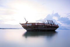 An old shipwreck or abandoned shipwreck. Wrecked boat abandoned stand on beach or Shipwrecked off the coast of Thailand Royalty Free Stock Photo
