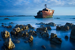 Old shipwreck long exposure on the rocks sunse Stock Image
