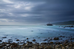 Old shipwreck long exposure on the rocks sunse Stock Photography
