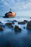 Old shipwreck long exposure on rocks at sunset Royalty Free Stock Photography