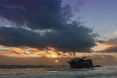 Old shipwreck long exposure on the rocks sunset Stock Photo