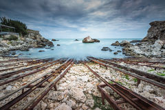 Old shipwreck long exposure on the rocks at sunset Royalty Free Stock Photography