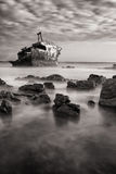Old shipwreck long exposure on rocks at sunset artistic conversi Royalty Free Stock Photography