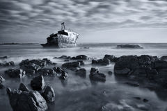 Old shipwreck long exposure on rocks at sunset artistic conversi Stock Images